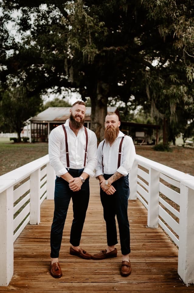 Groom and best man in overalls on catwalk at Grainery